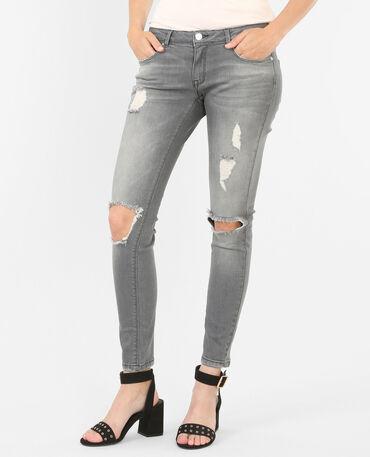 Jeans skinny con rotos en las rodillas gris