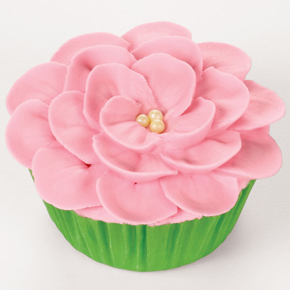 piping a flower on a cupcake wilton
