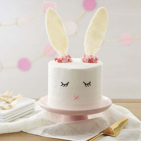 White five layer cake with white buttercream and an easter bunny face with candy ears