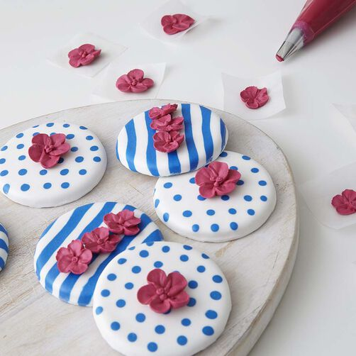 Round cookies with blue and white stripes and white with blue polka dots using royal icing.  Red apple blossoms sit on top.