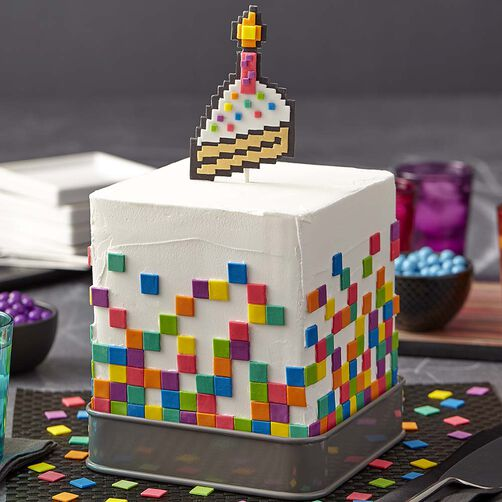 White cubed cake with fondant rainbow pixels and pixelated cake topper