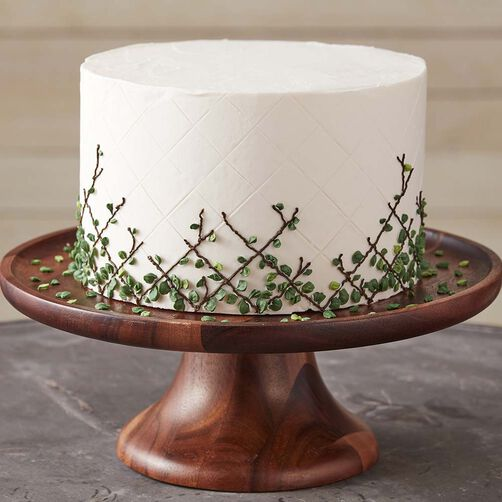 Minimalist white cake with delicate green leaves on a lattice