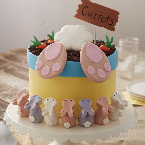 """Full view of a flower pot with what looks like a rabbit's feet and tail sticking out of the dirt, surrounded by carrots and a sign that says """"carrots"""". Small rice cereal bunnies surround the base of the flower pot, looking up at the larger rabbit's feet."""