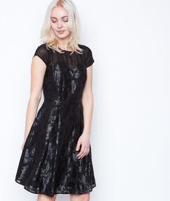 Vestido estilo evasé con motivos de tul negro.