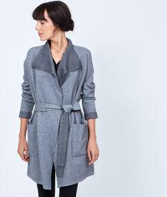 Gilet ceinturé long en tricot gris.