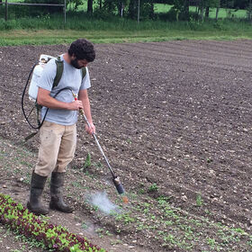 Man cultivating field with a Red Dragon Backpack Flame Weeder