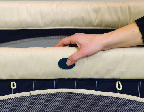 Push buttons on the sides of the Lullaby Playard allow the playard to quickly fold up for travel or storage