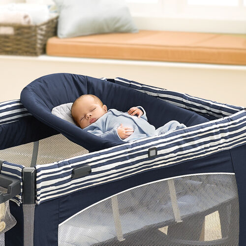 A quilted, angled baby napper provides a comfortable place for infants to nap with the Lullaby Baby Playard